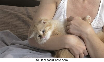 Woman with Ginger cat in bed