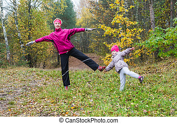 Woman with girl doing aerobics in the autumn park