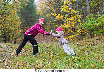 Woman with girl doing aerobics in the park