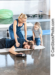 Woman with girl helping tired man lying on mat at gym