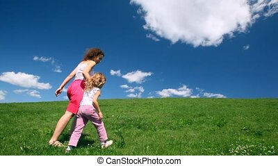 Woman with girl holding hands rise on hill