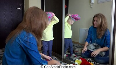 Woman with girl measure warm winter hats near mirror