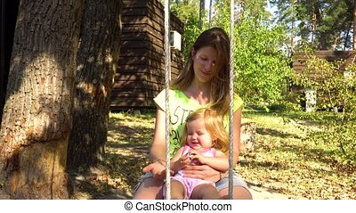 Woman with girl on wooden seesaw under tree - Young mother...