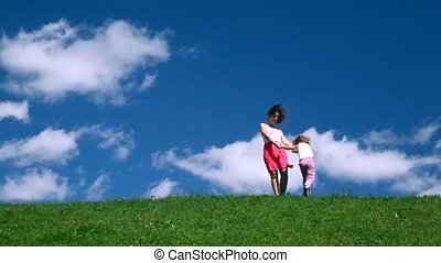 Woman with girl play on hill