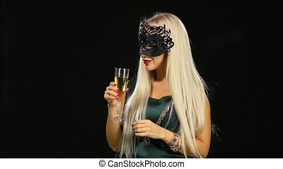 woman with glass of champagne wearing venetian masquerade...