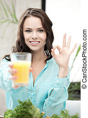 woman with glass of orange juice showing ok sign