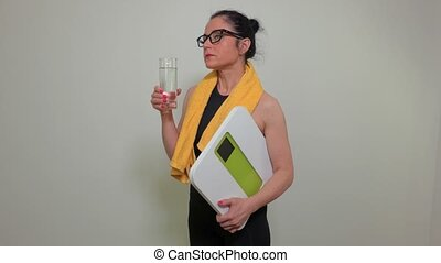 Woman with glass of water and electronic scale