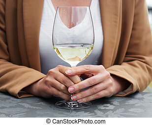 Woman with glass of white wine in restaurant.
