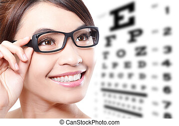 woman with glasses and eye test chart - beautiful woman with...