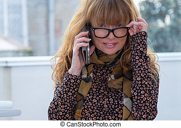 woman with glasses at home talking on mobile phone