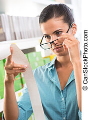 Woman with glasses checking a receipt