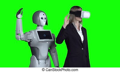 Woman with glasses of virtual reality raises has hand up and waves the robot repeats after her. Green screen. Slow motion