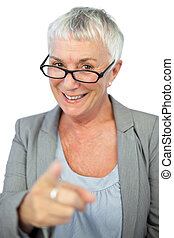 Woman with glasses pointing at camera