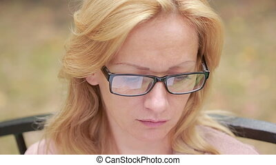 woman with glasses reading a book. close-up. reflected in the lenses of the book