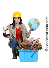 Woman with globe in hand kneeling by waste materials