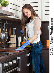 Woman with gloves cleaning kitchen