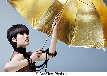 Woman with gold umbrella.