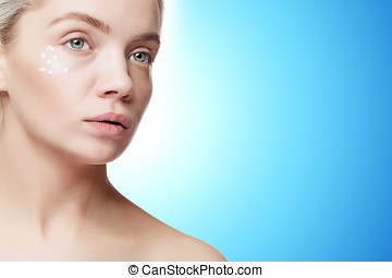Woman with good skin and cream drops on face