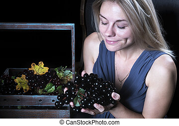 Woman with grapes in the dark