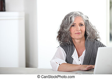 Woman with gray hair and computer