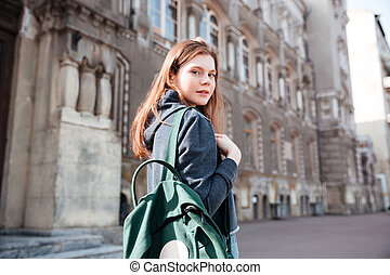 Woman with green backpack walking around old city