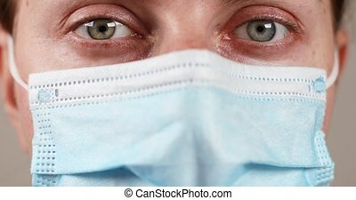 Close up female doctor in protective blue medical mask. Woman with green gray eyes looking at the camera and blinking. Stop the virus and epidemic diseases.