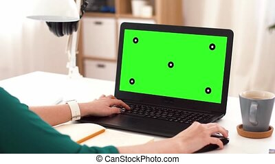 woman with green screen on laptop at home - technology, post...