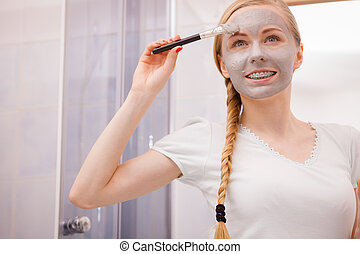 Woman with grey clay mud mask on her face
