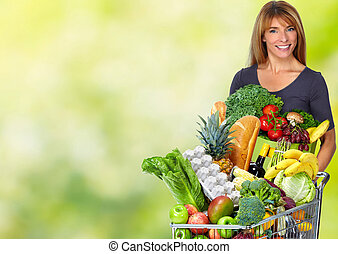 Woman with grocery bag of vegetables. - Woman with paper bag...