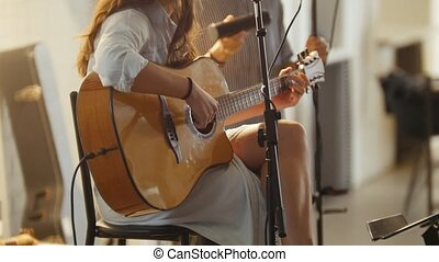 Woman with guitar at stage in loft - rock band - hipster's...