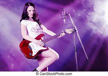 woman with guitar has fun in studio