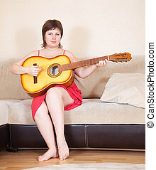 Woman with guitar in home