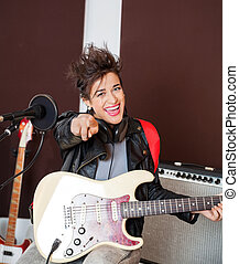 Woman With Guitar Pointing In Recording Studio