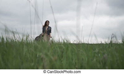 Woman with guitar walking in field