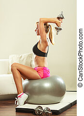 Woman with gym ball and dumbbell doing exercise