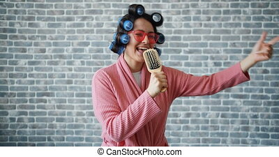 Woman with hair curlers, glasses and bathrobe singing in hairbrush having fun