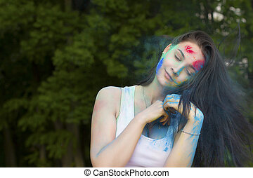 Woman with hair in motion covered dry paint