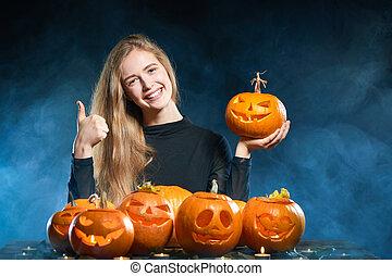 Woman with Halloween pumpkin gesturing OK