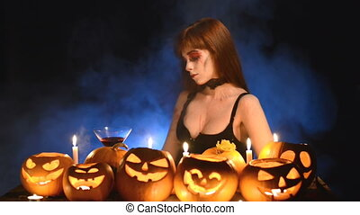 Woman with Halloween pumpkins holding cocktail glass
