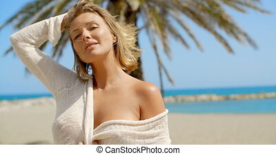 Woman with Hand in Hair on Beach Looking to Side