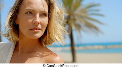 Woman with Hand in Hair on Beach Looking to Side - Blond...