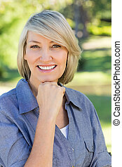 Woman with hand on chin in park - Portrait of beautiful...