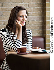 Woman With Hand On Chin Looking Away In Coffeeshop