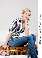 Woman With Hand On Chin Sitting On Overloaded Baggage