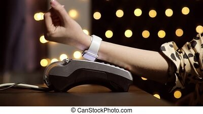 Woman with hand watches using terminal for payment, non-cash transaction, hand closeup, side view. Non-cash contactless payment concept. Pos-terminal on table on black background with yellow spots.