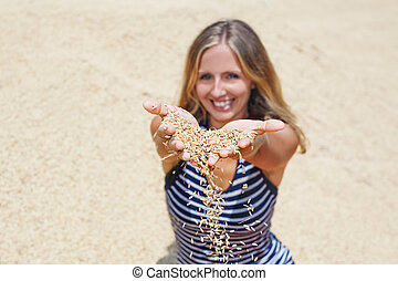 Woman with handful of raw rice grains in hands