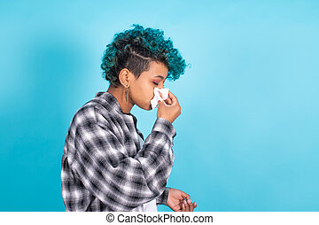 woman with handkerchief sneezing or with cold isolated on color background
