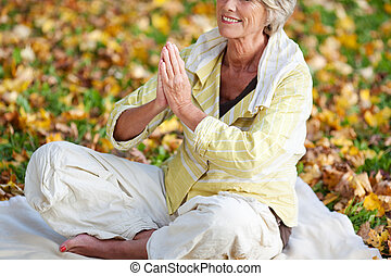 Woman With Hands Clasped Meditating In Park - Low section of...