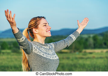 Woman with hands raised in nature.