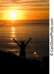 Woman with hands upheld at sunset - Woman with hands upheld...